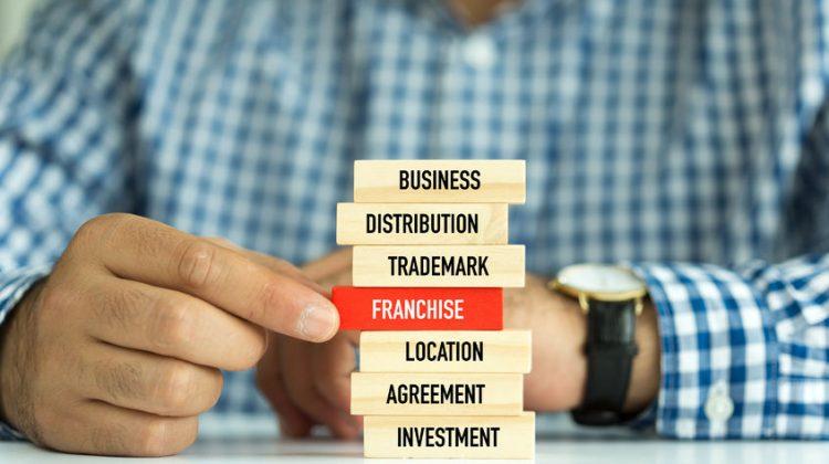 62482209 - businessman building franchise concept with wooden blocks
