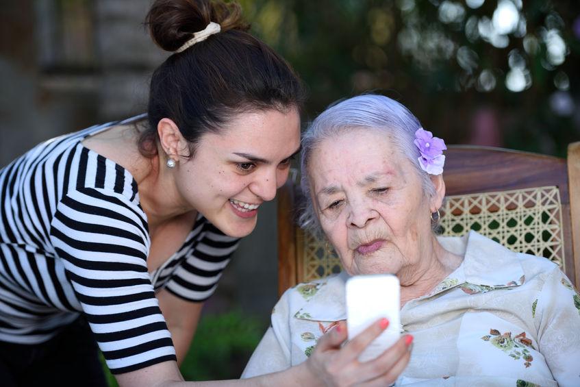 55650763 - grandchildren teaching grandma learning use white smartphone